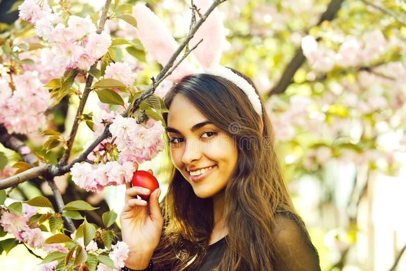 Oídos del conejito en mujer con las flores de Sakura de la primavera y el huevo de Pascua imagenes de archivo