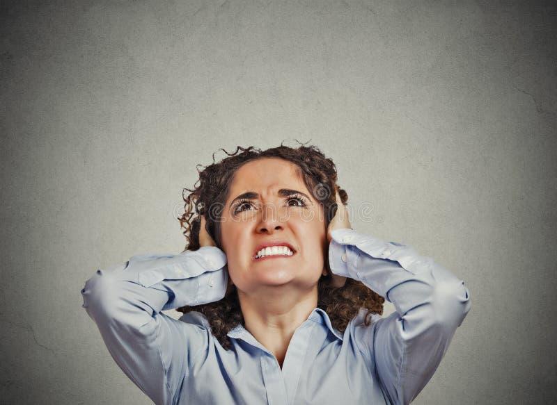 Oídos enojados de la cubierta de la mujer que miran para arriba fuerte ruido de la parada foto de archivo libre de regalías