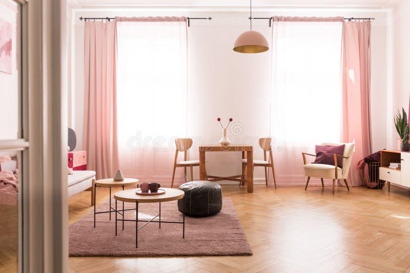 Обеденный стол со стулом в середине яркой пастельной розовой живущей комнаты в арендуемом доме стоковые изображения rf