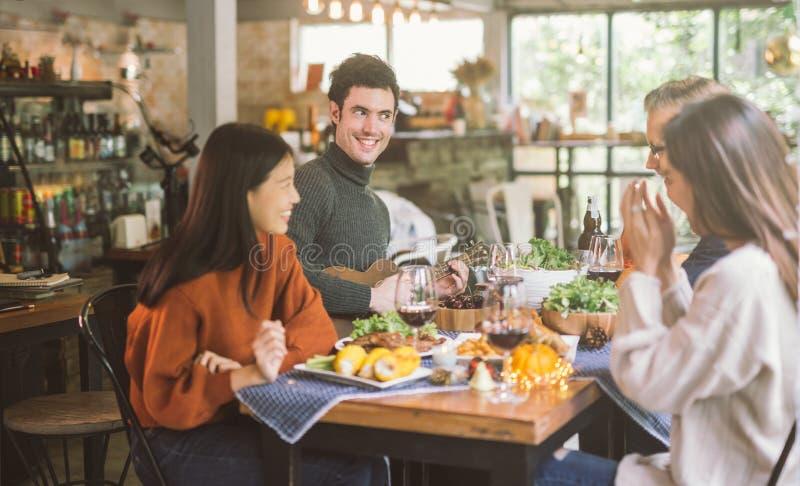 Обед с друзьями Группа в составе молодые люди наслаждаясь обедающим совместно стоковое фото