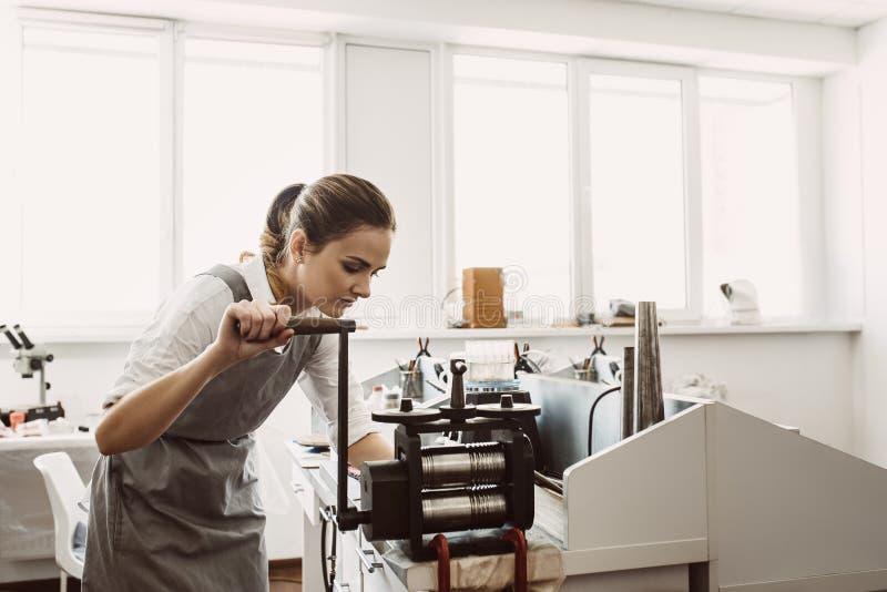 Обработка сырья Женский кузнец женщины производя металл на машине завальцовки ремесла стоковые фото