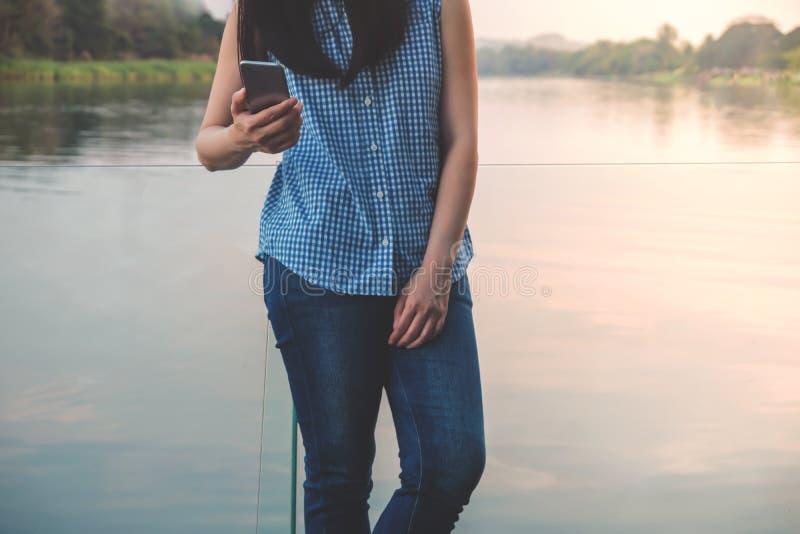 Образ жизни современной концепции людей Молодая женщина ослабляя путем читая данные или сообщение через смартфон стоковая фотография rf
