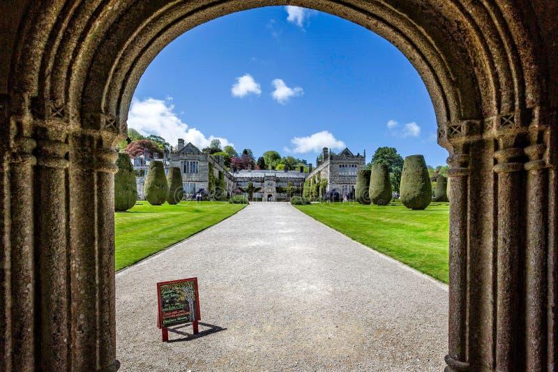 Обрамленный взгляд загородного дома Lanhydrock и великолепного сада фигурной стрижки кустов и официальных во фронте в Корнуолле,  стоковые фото
