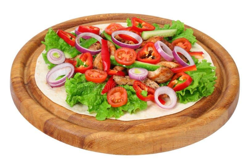 Обруч Tortilla с мясом и овощами жареной курицы на деревянной доске изолированной на белой предпосылке стоковое изображение