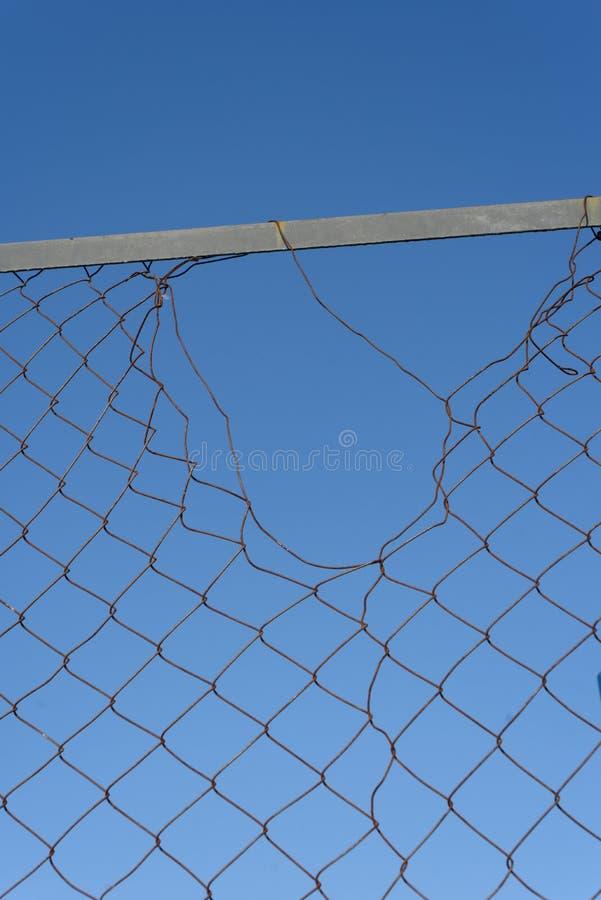 Обрыванная провод сетка ограждая с голубым небом стоковая фотография rf