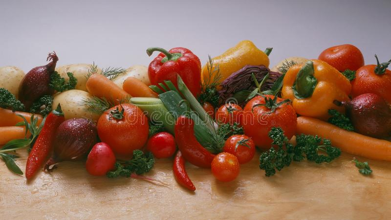 Vegetables - on a light background, on a wooden the table: tomatoes, cherry tomatoes on a branch, carrots, red onion stock photo