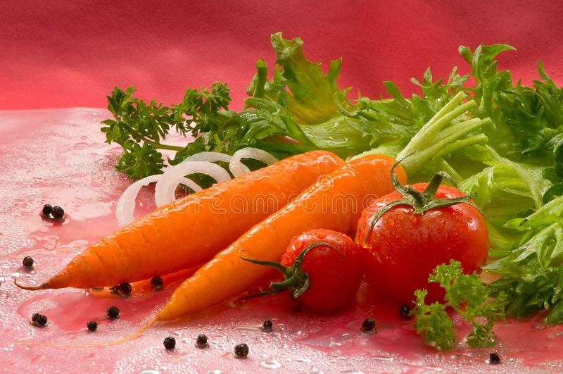 Vegetables - tomato, red pepper, peppercorns, green salad with water drops. On a red background stock photos