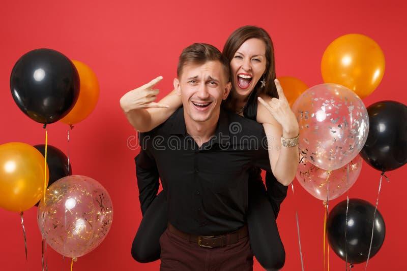 Оглушать молодые пары в черных одеждах празднуя партию праздника дня рождения на ярких красных воздушных шарах предпосылки стоковые фотографии rf