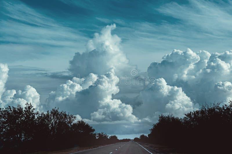 Оглушать небо с большими темными облаками и ландшафтом дороги стоковое фото