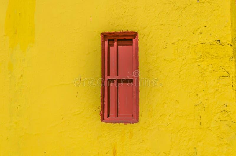 Окно красного цвета закрытое запертое в желтой стене стоковая фотография rf
