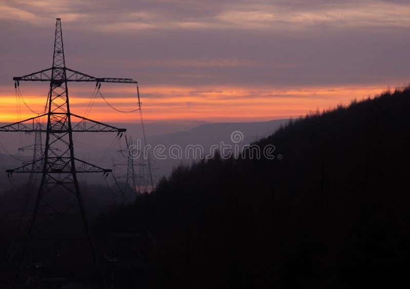 Опоры силы бегут через лес на заходе солнца в Великобритании, пиковом районе стоковое фото