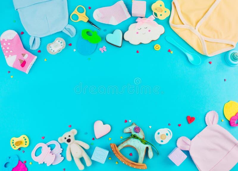 Одежды, игрушки и аксессуары младенца на голубой предпосылке с экземпляром стоковые изображения