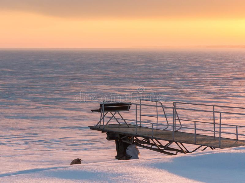 Lonely bench on the background of a winter sunset. Orange sunset fell on the shores of a frozen reservoir near Novosibirsk. The bench on the lonely pier is empty stock image