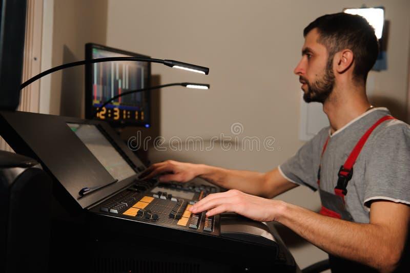 Освещая инженер работает с управлением техников светов на шоу концерта Профессиональный светлый смеситель, смешивая консоль стоковая фотография rf