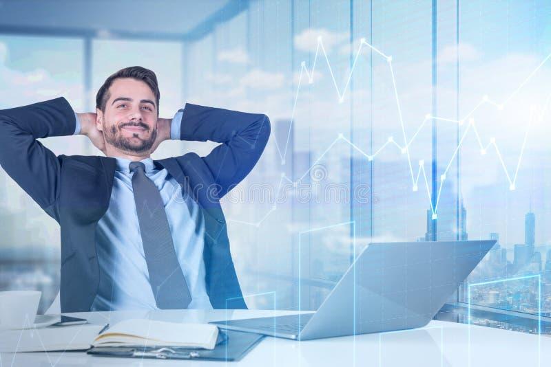 Ослабленный бизнесмен с ноутбуком в офисе, изображает диаграммой стоковое изображение