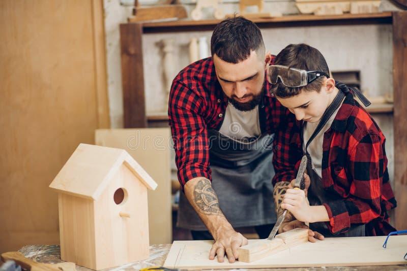 Отец и его сын работая совместно в деревянной мастерской, строя birdhouse стоковая фотография
