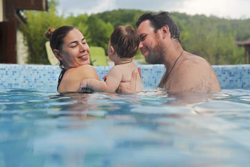 Отец и мать уча небольшому плаванию ребенка в бассейне стоковые фотографии rf