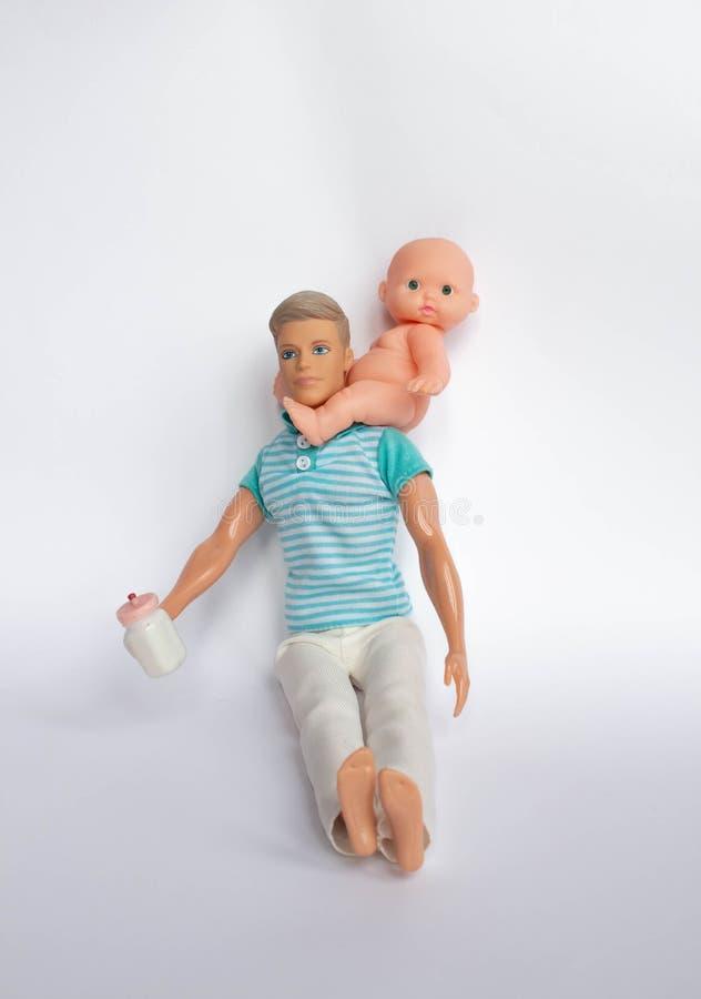 Отец и сын, куклы на белой предпосылке, отец держат сына в его оружиях, кормят его сына Заботить для семьи стоковые фото