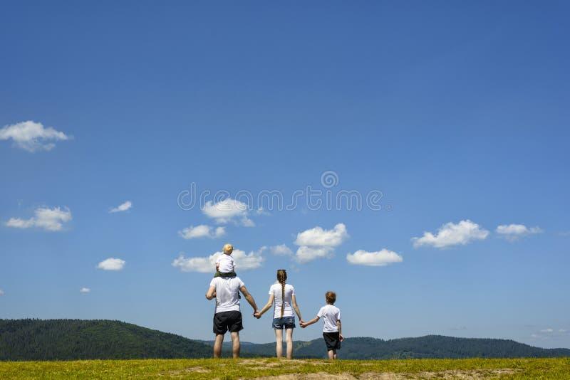Отец, мать и 2 маленьких сынов стоят на зеленом поле на предпосылке лесистых холмов, голубого неба и облаков Семья стоковые изображения rf