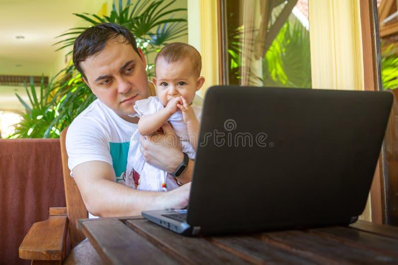 Отец с младенцем на руках Забота работы и младенца Человек работая с ноутбуком в перемещении стоковая фотография rf