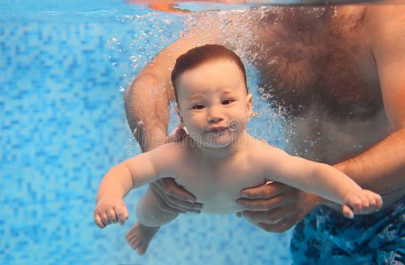 Отец уча небольшому плаванию ребенка под водой в бассейне стоковые фотографии rf