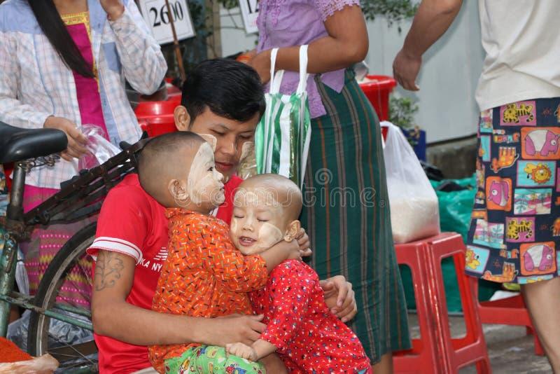 Отец Myanmese и 2 дет с порошком Мьянмы thanakha на их сторонах, играя потеху счастливо совместно в рынке стоковые фотографии rf