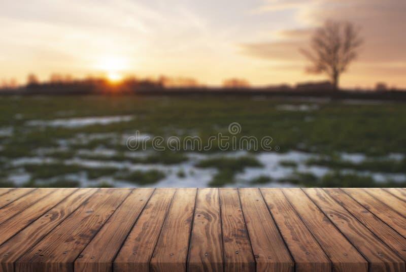Открытый космос для вашей рекламы, старый деревянный стол на предпосылке предыдущей весны, сельского ландшафта на заходе солнца в стоковые изображения