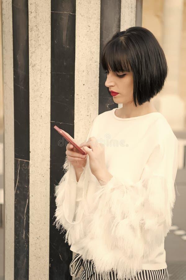 Отмененная дата посылает сообщение Дама девушки модная с предпосылкой smartphone стиля причёсок bob отправляя СМС внешней городск стоковые фотографии rf