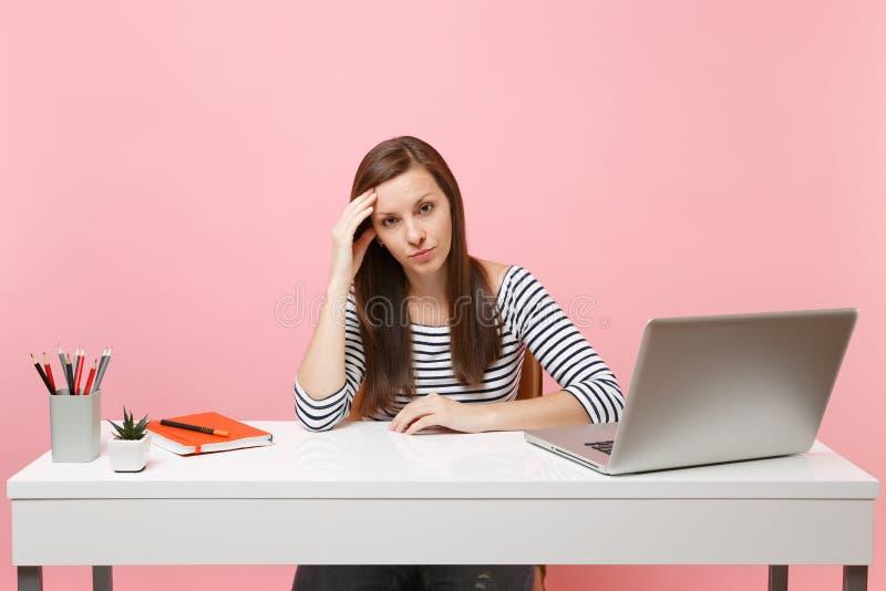 Относят расстроенная уставшая женщина полагаясь в наличии для того чтобы сидеть, работа на белом столе с современным изолированны стоковые фото