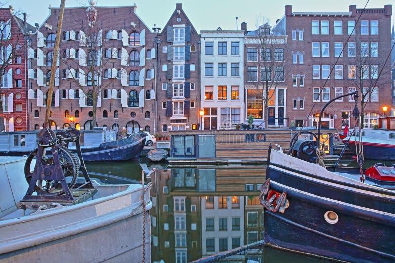 Отражение красочных зданий наследия вдоль канала Brouwersgracht в Амстердаме, с плавучими домами на переднем плане стоковое фото rf