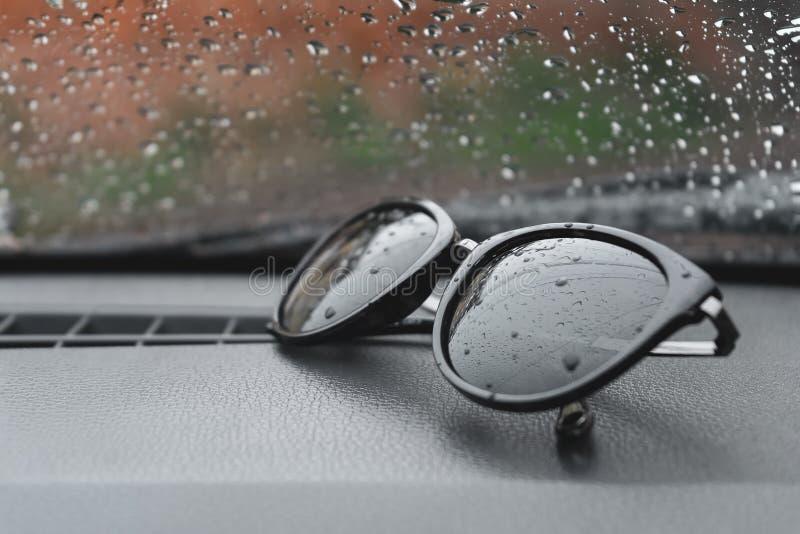 Отражение падений дождя в солнечных очках которые лежат на панели в автомобиле стоковые фото