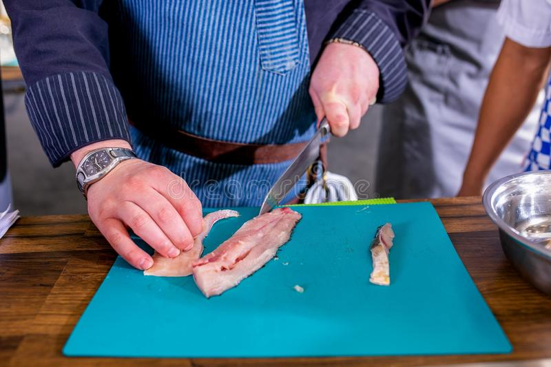 Отрезки шеф-повара удят в части Мастерский класс в кухне Процесс варить Шаг за шагом консультационо Конец-вверх стоковые фото