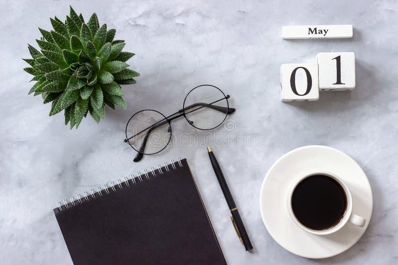 Офис или домашний стол таблицы Деревянный блокнот черноты 1-ое мая календаря кубов, чашка кофе, суккулентная, стекла на мраморе стоковая фотография rf