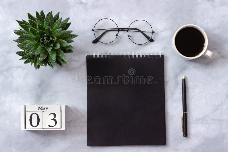 Офис или домашний стол таблицы Деревянный календарь 3-ье мая кубов Черный блокнот, чашка кофе, суккулентная, стекла на мраморе стоковые изображения