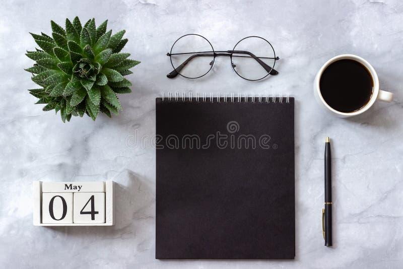 Офис или домашний стол таблицы Деревянный календарь 4-ое мая кубов Черный блокнот, чашка кофе, суккулентная, стекла на мраморе стоковая фотография