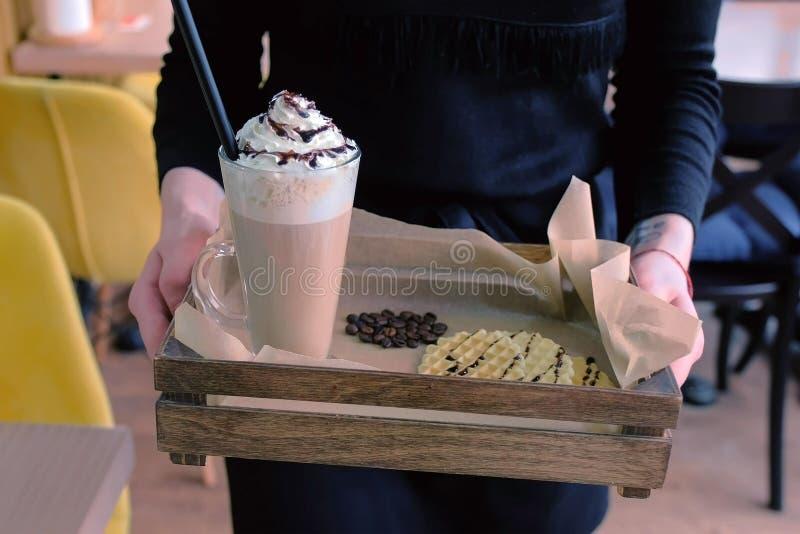Официант носит заказ к клиенту ирландский кофе служил с вафлями на подносе Конец-вверх рук стоковое изображение
