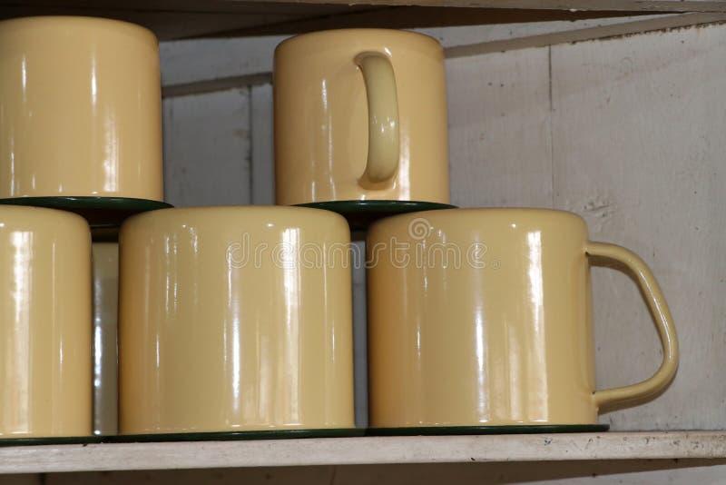 Оцинковывайте чашку в сливочного цвета положенное перевернутое и штабелированный стоковые фото