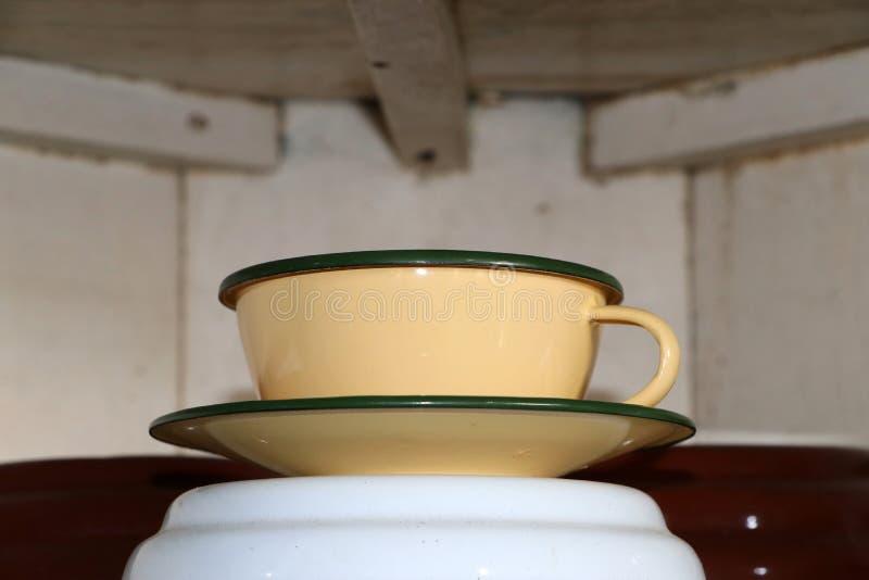 Оцинковывайте чашку и поддонник в сливочного цвета это античная чашка стоковая фотография