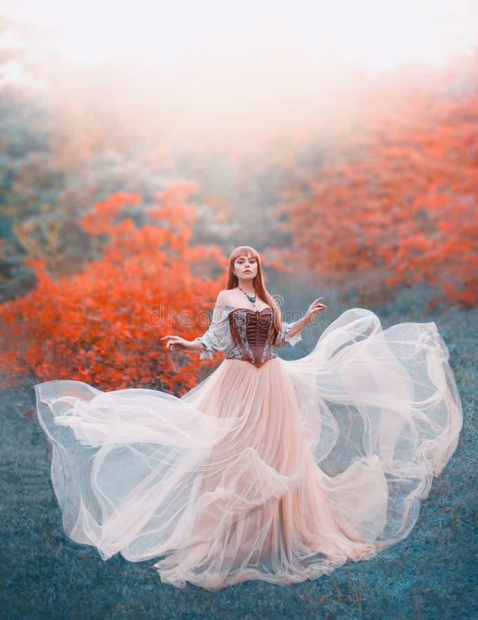 Очаровательная привлекательная девушка с платьем света персика длинного летания развевая винтажным стоит самостоятельно в лесе, н стоковое фото