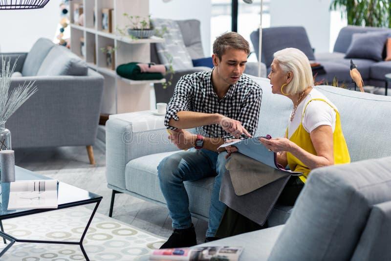 Очаровывая старея дама обсуждая образцы ткани с сыном в магазине стоковые фото