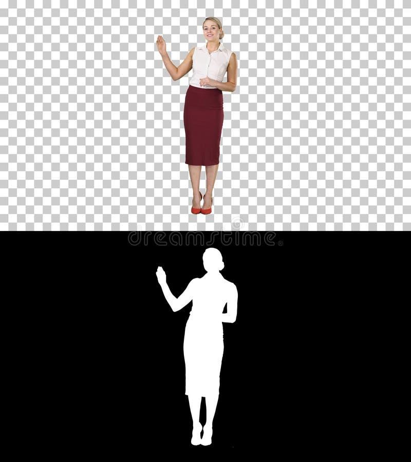Очаровывая усмехаясь энергичная женщина в официальных одеждах говоря с камерой и указывая на стороны, канал альфы стоковые изображения