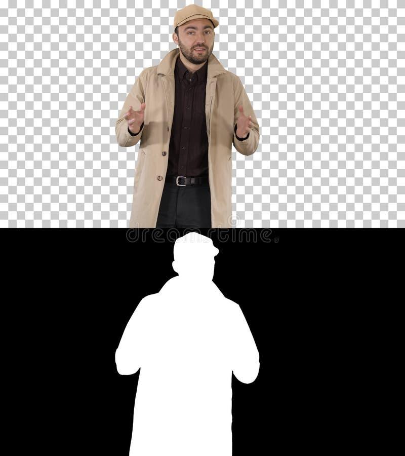 Очаровывая человек в пальто канавы идя и говоря к камере, каналу альфы стоковые фотографии rf