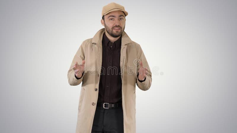Очаровывая человек в пальто канавы идя и говоря к камере на предпосылке градиента стоковые изображения rf