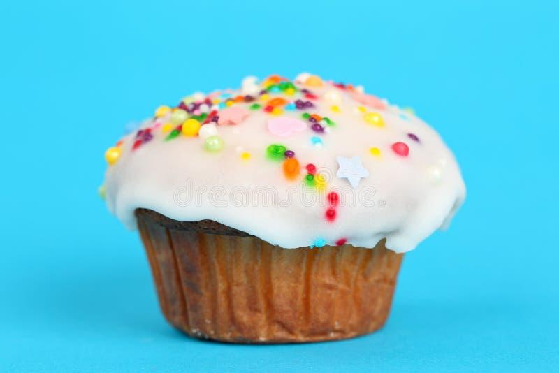 Очень вкусная домодельная булочка с белой замороженностью помадки и красочным сахаром брызгает на яркой предпосылке сини бирюзы п стоковое изображение rf