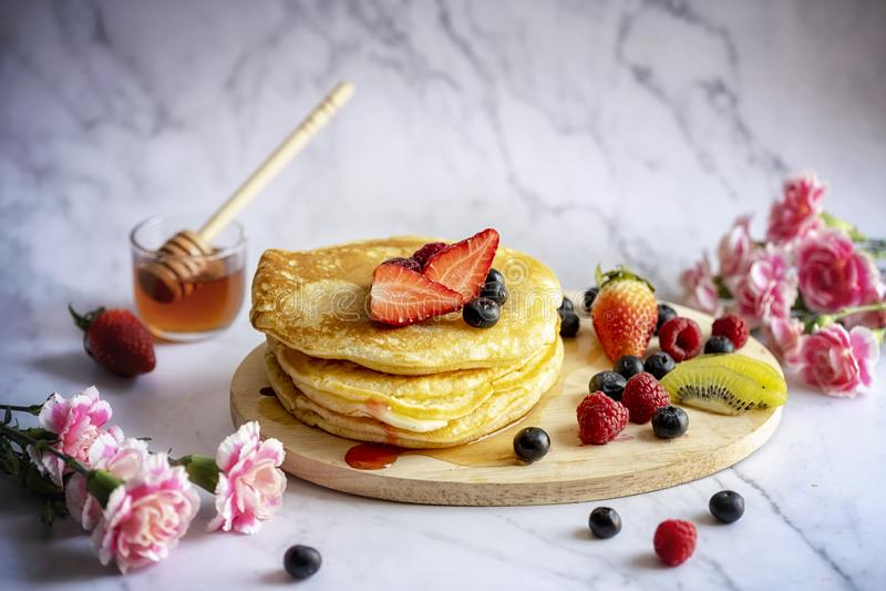 Очень вкусные блинчики со свежими ягодами и медом на мраморном сделанном по образцу поле Гвоздика и предпосылка переднего плана р стоковое фото