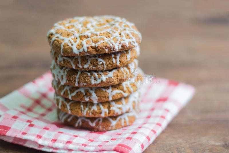 Очень вкусные хрустящие печенья овсяной каши украшенные с белой поливой на деревянной предпосылке, концом-вверх стоковые фотографии rf