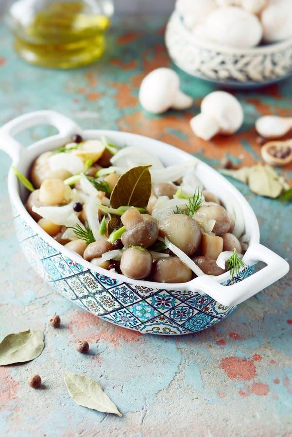 Очень вкусные marinated грибы в красивом шаре с луками, перцем, укропом и оливковым маслом на сер-голубой предпосылке, взглядом с стоковая фотография