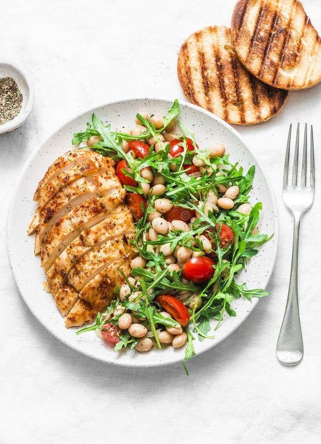 Очень вкусный здоровый обед - испеченные куриная грудка и белые фасоли, arugula, салат томатов вишни на светлой предпосылке стоковые фото