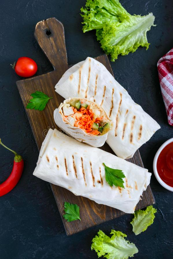 Очень вкусный сэндвич shawarma на черной предпосылке Обручи буррито с зажаренными цыпленком и овощами, зелеными цветами стоковое фото