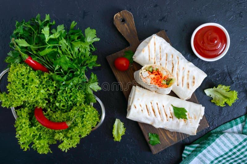 Очень вкусный сэндвич shawarma на черной предпосылке Обручи буррито с зажаренными цыпленком и овощами, зелеными цветами стоковое изображение rf